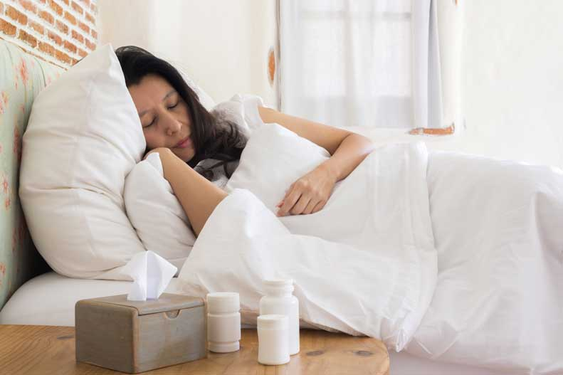 A sick woman sleeps next to a box of tissues and some medicine bottles.