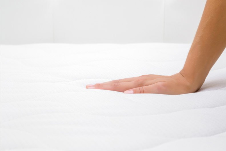 A woman presses her hand into her mattress.