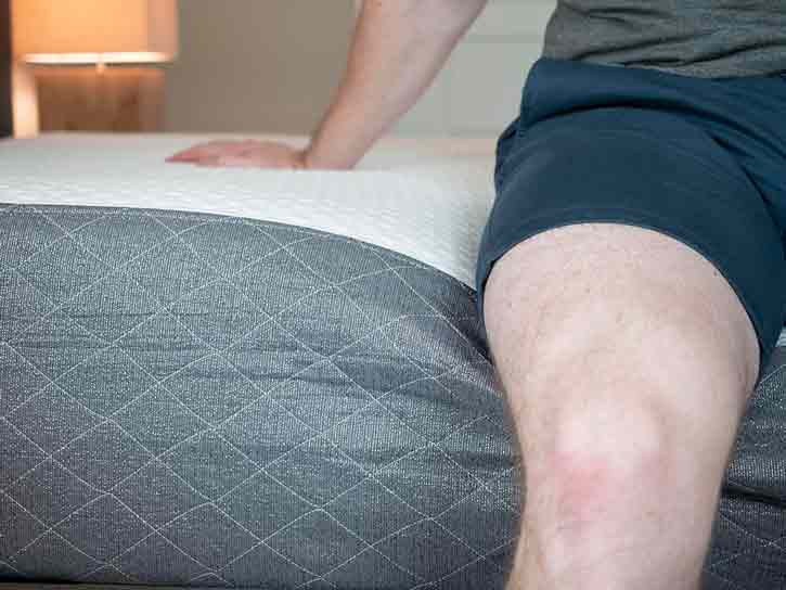 A man sits on the edge of a mattress