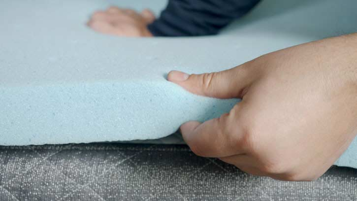 A man squeezes a memory foam mattress topper.