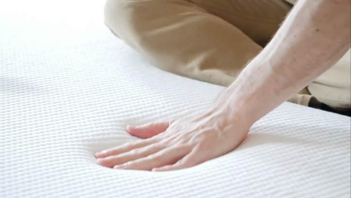 A man pushes into a mattress.