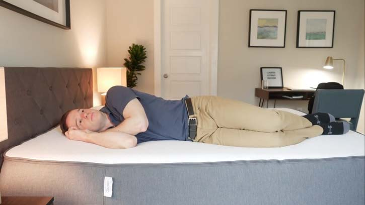 A man sleeps on his side on a hybrid mattress.