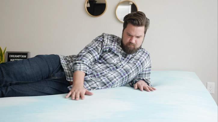 A man lies down on a memory foam mattress topper.