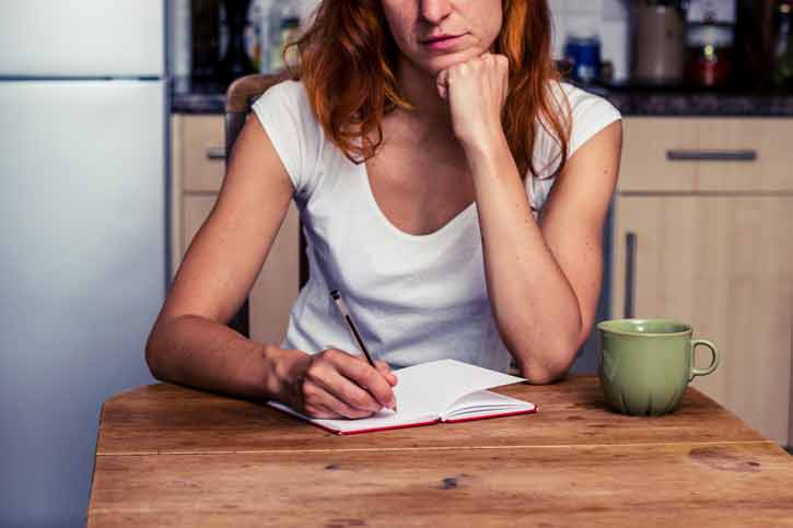 A woman takes notes in her journal.