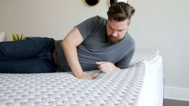 A man feels the top of a mattress topper