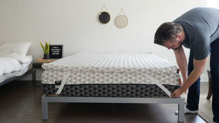 A man places a topper on a mattress