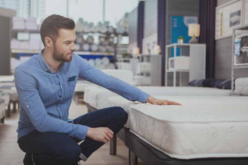 A man shops for a new mattress.