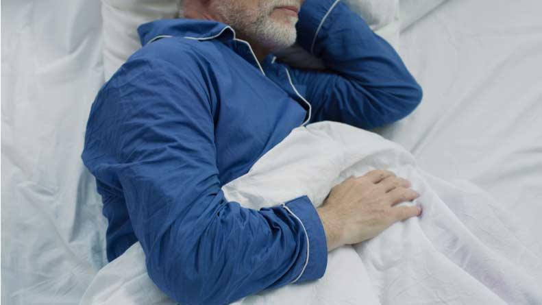 An older man sleeps wearing pajamas.