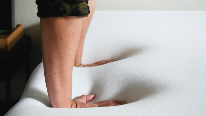 A man pushes into a mattress.