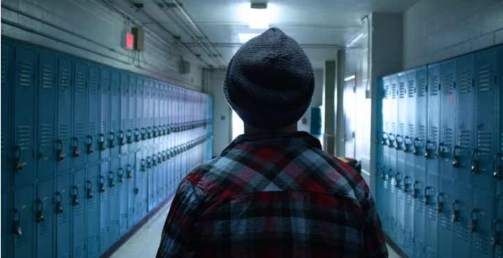 A teen walks down a long hallway.