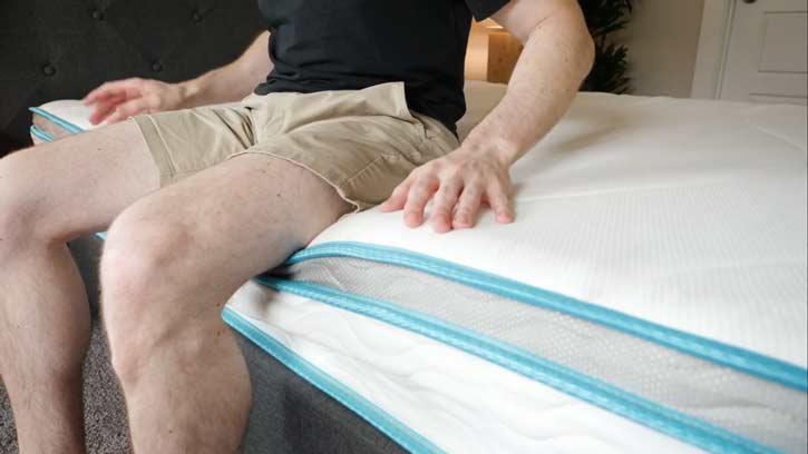 A man sits on the edge of a hybrid mattress.