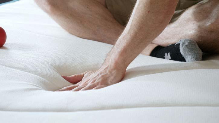 A man presses his hand into a mattress.
