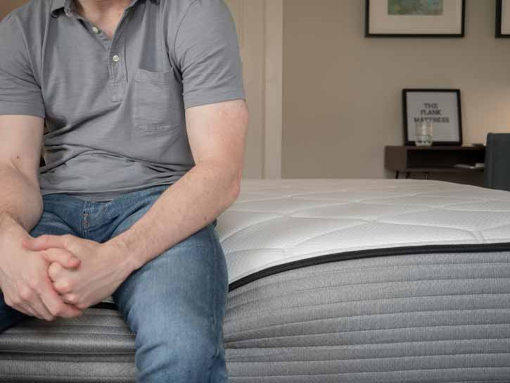 A man sits on the side of his mattress.