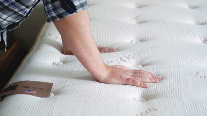 A man places his hand on a pillow top mattress.
