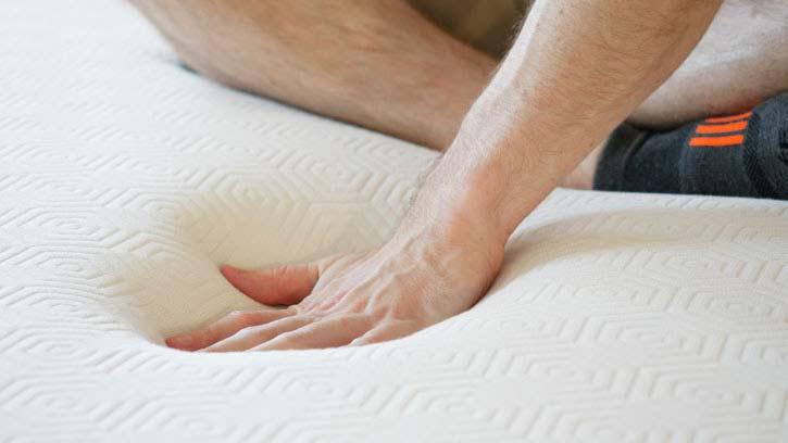 A man presses into the top of a mattress.