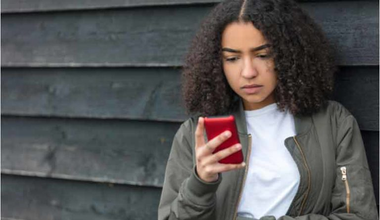 A sad young woman looks at her phone.