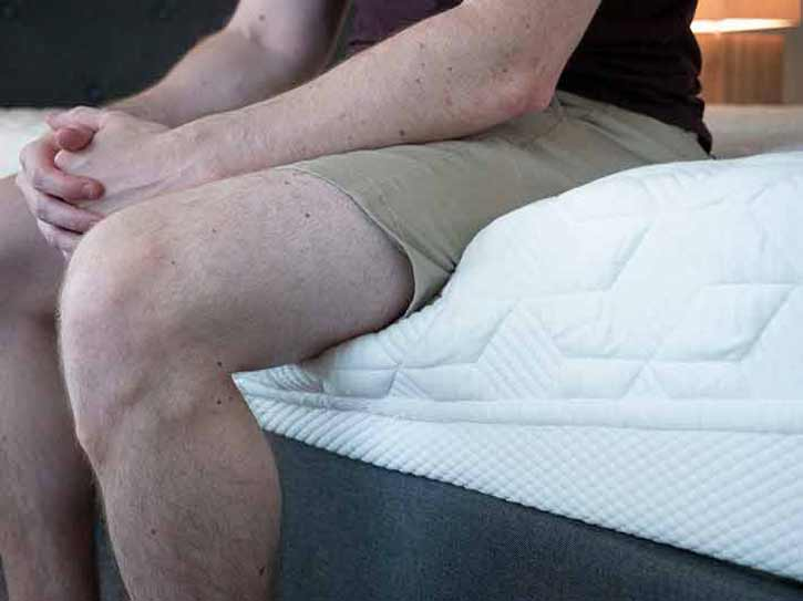 A man sits near the edge of an online mattress.