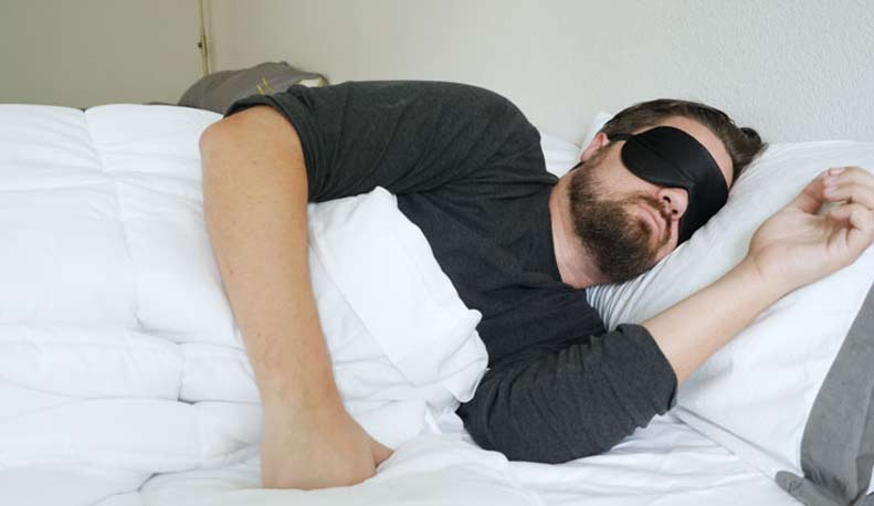 A man sleeps on his side while wearing a sleep mask.
