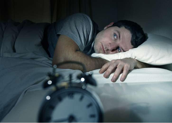 A man lies awake in bed.