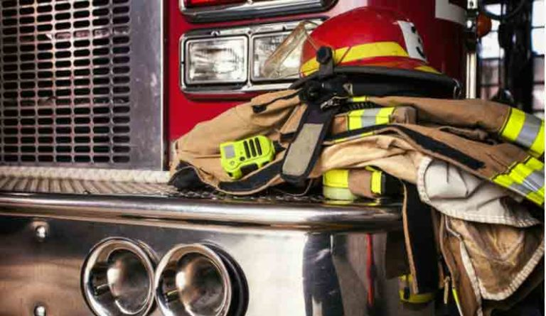 A closeup of firefighter gear sitting on the bumper of a firetruck.