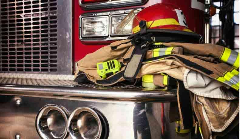 A closeup of firefighter gear sitting on the bumper of a firetruck.