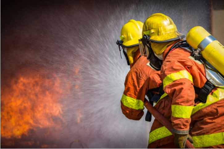 Firefighters spray water into a fire.