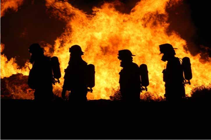 Firefighters walk by a raging fire.