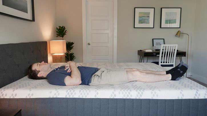A man lies on his back on a hybrid mattress.
