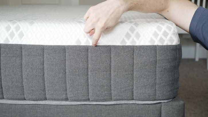 A man points to the different layers of a mattress.