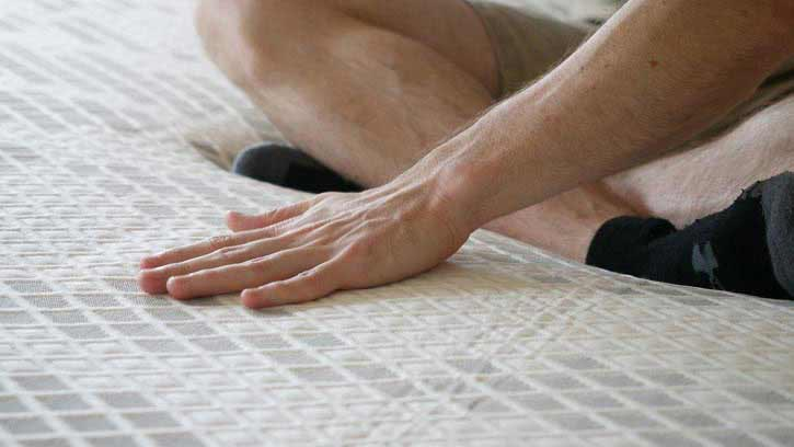 A man lays his hand on top of a mattress.