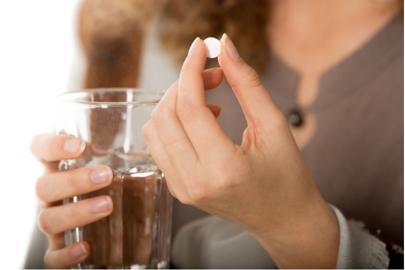 Woman Holding Sleep Aid and Glass of Water