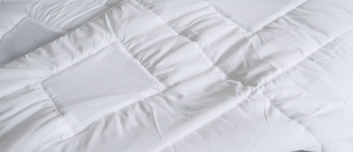 A white comforter with breathable mesh squares.