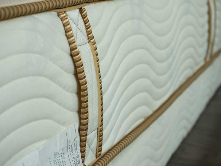 A view of the side of the Saatva Youth mattress with handles and organic fabric.