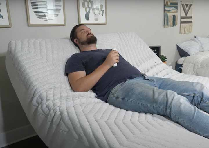 A man lies on an adjustable base in his bedroom