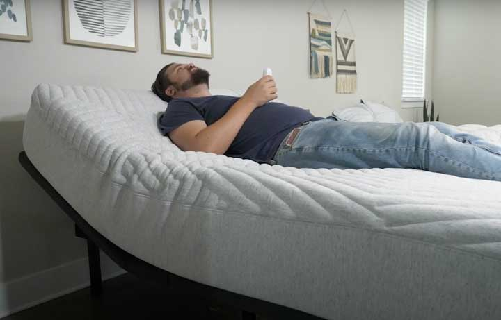 A man lies on the Casper Adjustable base with the head area slightly inclined